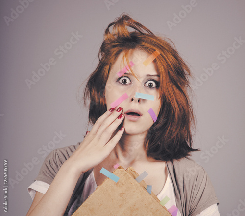Photo Red-haired businesswoman with book and notes on face.