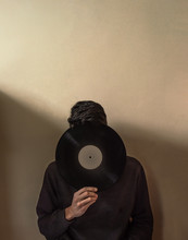 Young Man Cover His Face With A LP Vinyl Record. Vintage Or Retro Image With Beige Background And Copy Space. Concept Of Hiding In The Music.