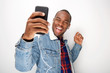 happy young black guy listening to music with smart phone and earphones and dancing