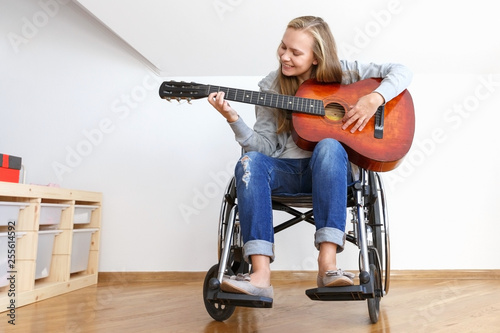 Photo  Invalid girl on wheelchair plays the guitar in day room.