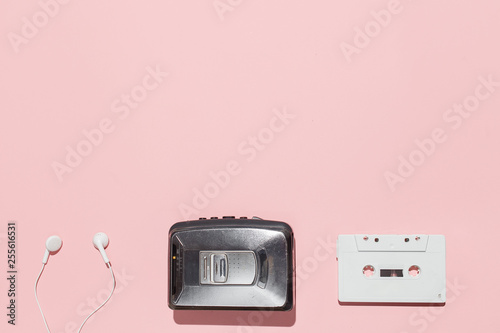 White audio cassette and cassette pleer with headphones on a pink background. Party 90s concept. - 255616531