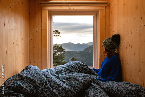 Tableau sur Toile Adventure young girl in a wooden cabin glamping contemplating the landscape thro