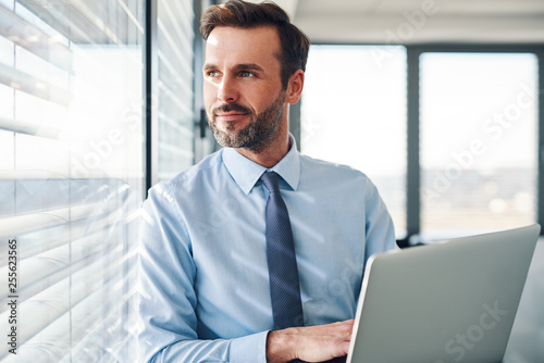Fotomural Handsome businessman standing with laptop, looking throught the window in modern