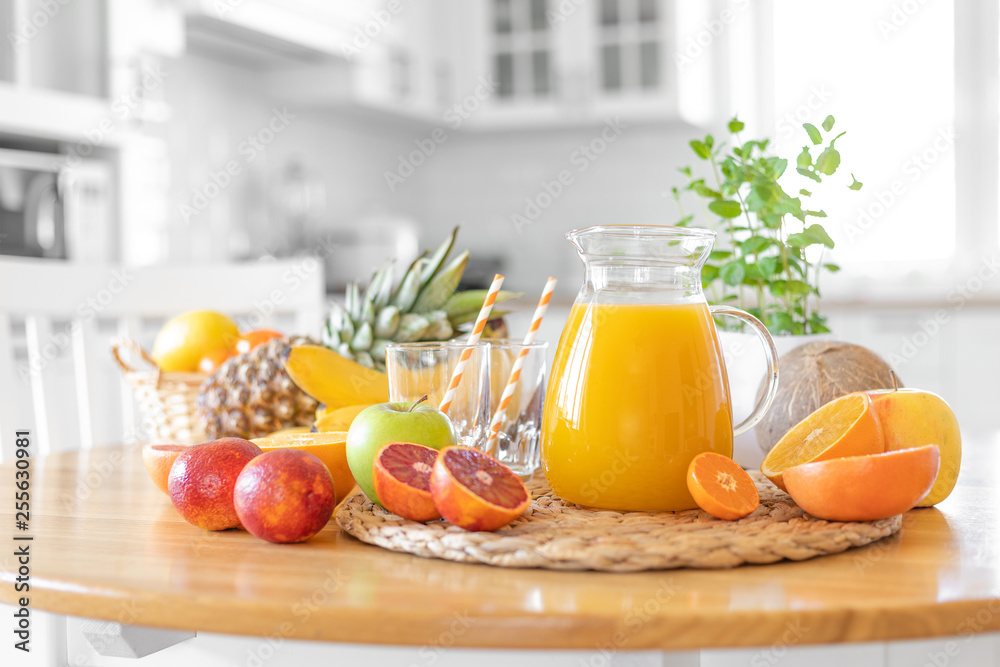 Fototapeta Multifruit juice and fresh fruit on table on kitchen background closeup