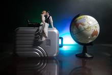 Just Married Travel Concept. Artwork Table Decoration With Couple Near Suitcases Ready To Honeymoon. Dark Blue Background.