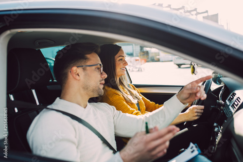 Driving school or test. Beautiful young pregnant woman learning how to drive car together with her instructor.