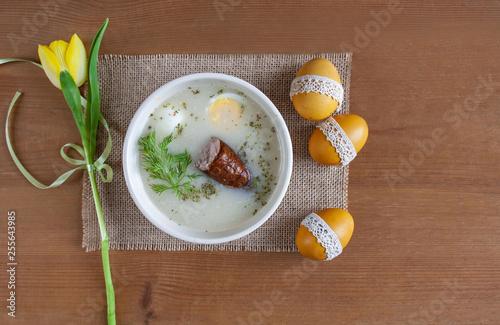 Fototapeta  Wielkanocne śniadanie - żurek z jajkiemi i kiełbasą, obok pisanki, koszyczek ze świeconką obraz