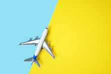 Model Airplane, Plane On Yellow And Blue Background. Directly Above. Travel, Vacation, Summer Concept. Top View, Flat Lay Composition. Copy Space.