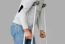 Man On Crutches On A Gray Back...