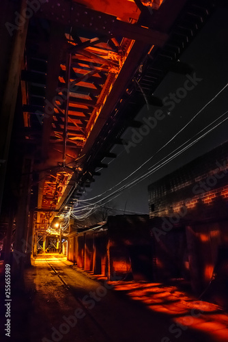 Canvas Prints Narrow alley Scary urban city alley with elevated illuminated vintage railway tracks at night in Chicago