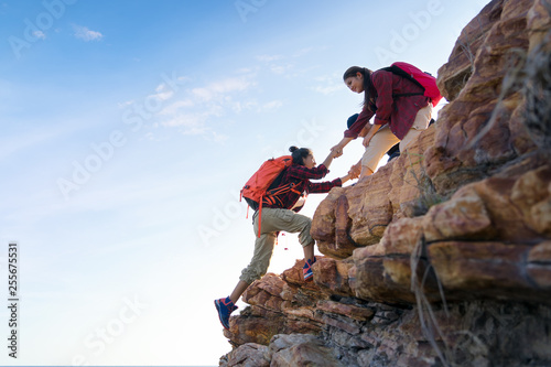 Leinwand Poster Young asian couple climbing up on the mountain,hiking and team work concept