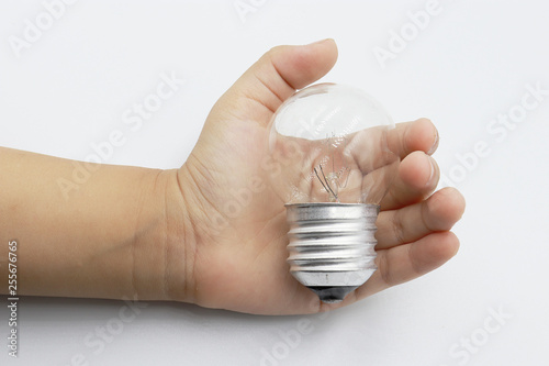 Fotografie, Obraz  Kids hand holding a light bulb isolated on white background.