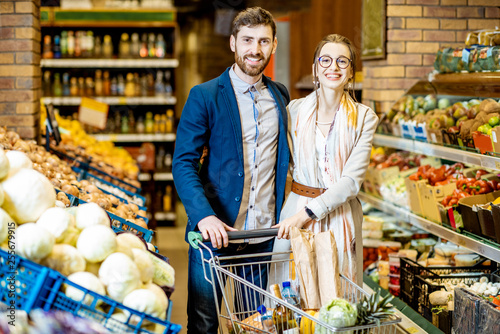Portrait Of A Young And Happy Couple Standing With Shopping