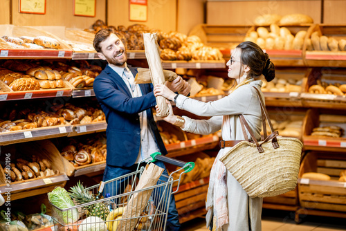 Deurstickers Bakkerij Man and woman having fun fighting with baguettes while shopping food in the supermarket
