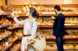 Man and woman choosing fresh pastries in the bakery department of the supermarket