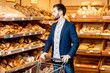 Handsome businessman choosing fresh pastries in the bakery department of the supermarket