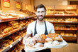 Portrait of a handsome baker in uniform standing with fresh pastries in the bakery deparment of the supermarket