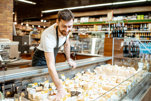 Fotomural  Shop worker laying out cheese pieces into the refrigeration showcase in the supe