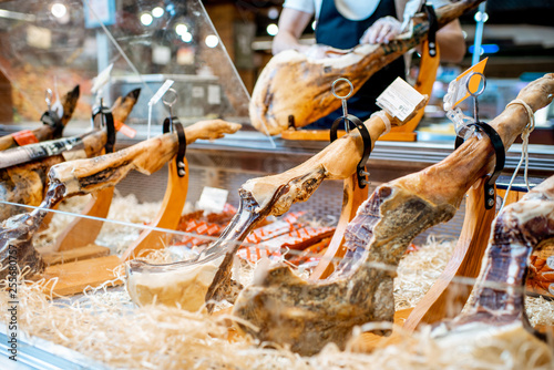 Photo Stands South America Country Jamon at the refrigerator counter with man slicing meat on the background in the supermarket