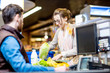 Young and cheerful woman putting products on the cash register buying food in the supermarket