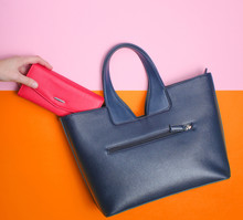 Female Hand Takes Red Wallet From Leather Bag On Pastel Background. Top View, Flat Lay, Minimalism