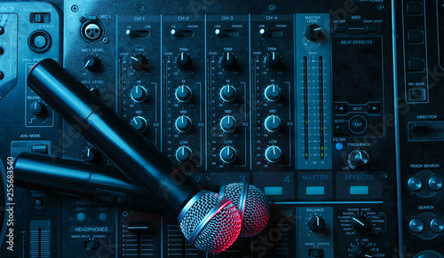 Night club, nightlife concept. Disco. Two microphone on DJ remote. Neon red blue light - 255683540