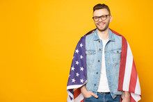 American Happiness. Smiley Man In Denim Shirt And Jeans With Hands In Pouches Next To The Yellowish Background With American Flag Over His Shoulders As A Symbol Of Happiness.