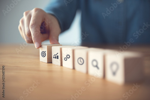 Woman hand arranging wood block with icon business strategy and Action plan Fototapeta