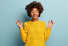 Satisfied Dark Skinned Young Woman Makes Okay Gesture With Both Hands, Keeps Eyes Closed, Dressed In Yellow Clothes, Practices Yoga After Work, Isolated Over Blue Studio Backround. Body Language
