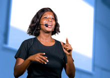 Successful Black Afro American Entrepreneur Woman With Headset Speaking In Auditorium At Corporate Training Event Or Seminar Giving Motivation And Success Coaching