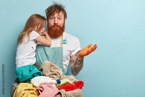 Obraz Busy overloaded father looks after little daughter and does household chores, has puzzled fatigue expression, has much work, washes clothes, spreads hand in bewilderment, isolated on blue wall - fototapety do salonu