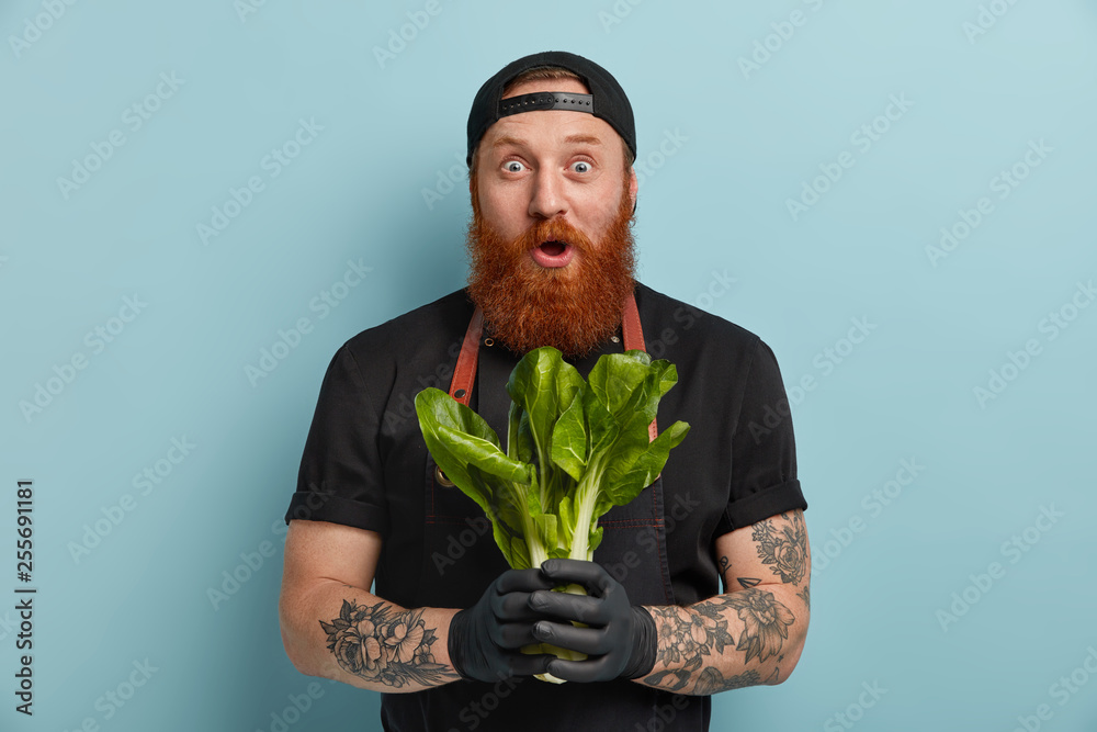 Fototapety, obrazy: Cooking, culinary, healthy nutrition concept. Positive surprised ginger bearded cook shocked to have no time for preparing dish, finds out recipe of taste dish, wears black uniform, stands indoor