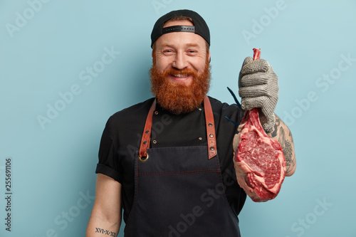 Fotografie, Obraz  Glad cheerful butcher suggests to taste beef or pork, works on meat factory, cuts on small pieces for selling, wears special uniform, isolated over blue background