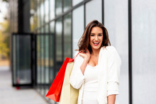 Beuatiful Young Long Hair Woman With Shopping Bags On Her Hands Smile At The Street