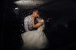 The bride and groom kissing in the car late at night, and it's raining outside. Bride and groom photographed behind the wet glass