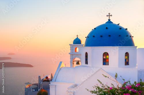 Fototapeta Church with blue dome at sunset on Santorini island, Greece. obraz