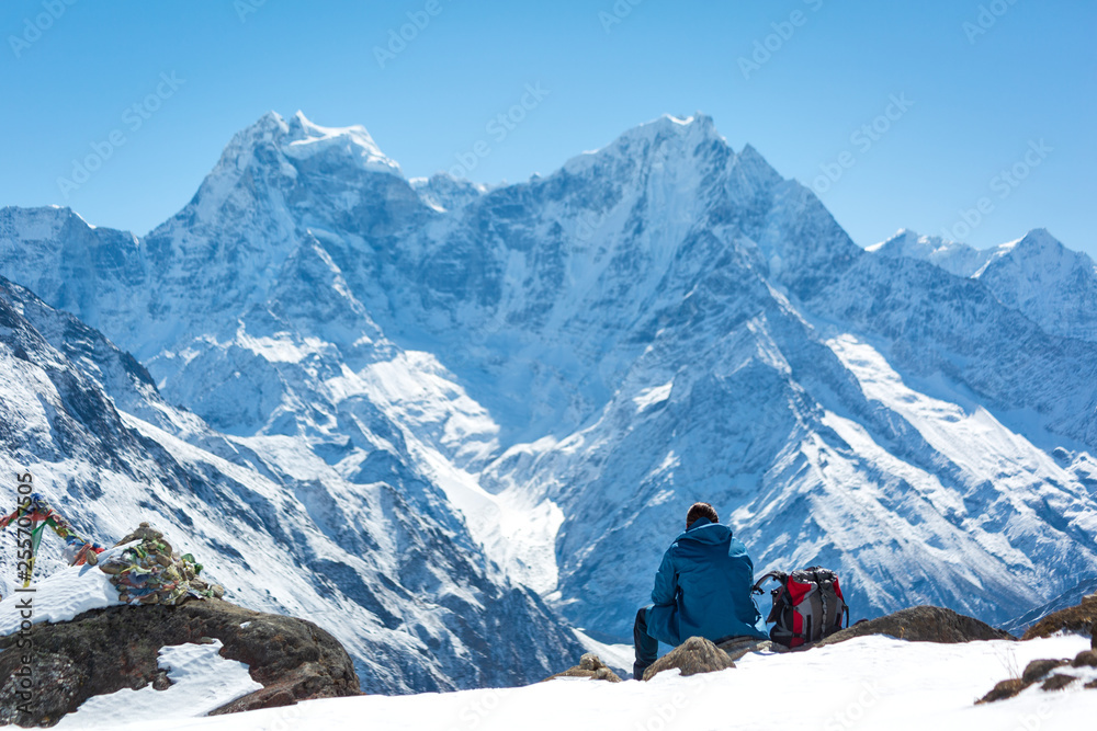 Fototapety, obrazy: A man sits in the mountains on a hill and looks at the horizon. Think about life. Lying next to the backpack. Everest trekking. Himalayas. Nepal