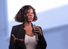 Confident Black African American Business Woman With Microphone Speaking In Auditorium At Corporate Event Or Seminar Giving Motivation And Success Coaching