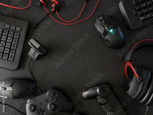 Fotografie, Tablou  gamer workspace concept, top view a gaming gear, mouse, keyboard, joystick, headset, mobile joystick, in ear headphone and mouse pad on black table background with copy space