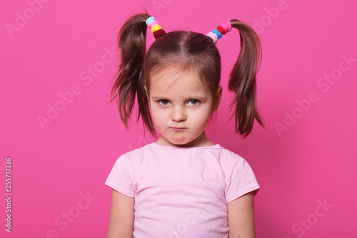 Sad little girl stands against pink wall, looks at camera. Cute kid wears rose t shirt, has two fanny poni tails with many colourful scrunchies, looks hurt with pouty lips. Upset child on playground. - 255713336