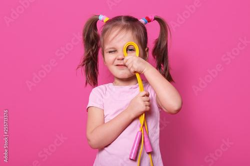 Fotografie, Obraz  Portrait of emotional beautiful girl, wears rose t shirt with two pony tails