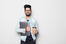 Portrait Of Handsome Casual Indian Man Drinking Coffee While Holding Laptop Computer, Standing On White Background