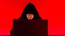 An Evil Hacker In A Black Mantle Is Working At A Computer On A Cyber Attack In The Office In Red. Anonymous User Hacks Database