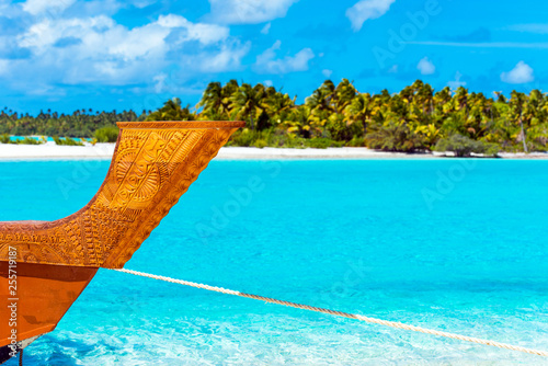 Poster Turquoise Wooden carved boat on a sandy beach in Aitutaki island, Cook Islands, South Pacific. With selective focus.