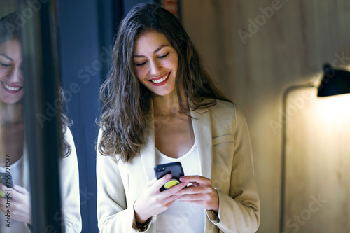 Fotografie, Obraz  Smiling young businesswoman texting with her mobile phone standing in advertising agency