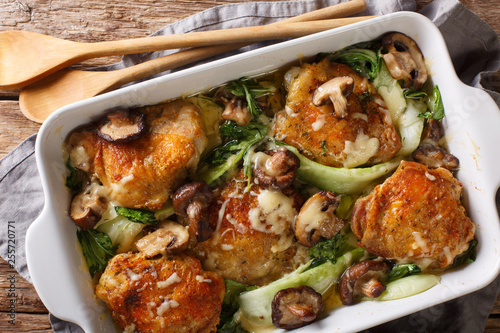 Fototapeta chicken thighs with baby bok choy, shiitake mushrooms and cheese sauce in a rustic style close-up. horizontal top view from above obraz
