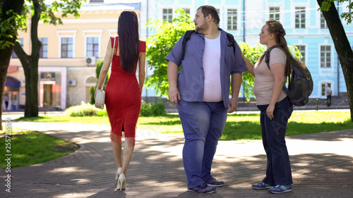 Fotografie, Obraz  Fat man looking at beautiful lady in red passing by, obese girlfriend jealous