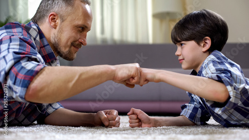 Fotografiet  Stepfather and child fist bumping, partnership greeting, happy childhood moment