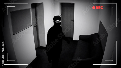 Photo Robber in mask looking surveillance camera, corporative building protection