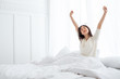 Asian woman wake up in the morning, sitting on white bed and stretching, feeling happy and fresh